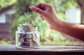 Hand putting money coins  with filter effect retro vintage style — Stock Photo