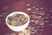 Coin in the cup with filter effect retro vintage style — Stock Photo