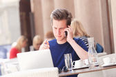 Young Man Sitting and Talking on Phone — Stock Photo