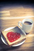 Delicious slice of bread with strawberry jam heart shape — Stockfoto