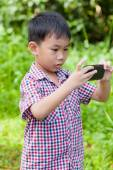 Little boy taking photos by digital camera on smartphone with go — Stock Photo