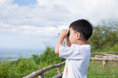 Little child look in binoculars outdoor in sunny summer day  — Stock Photo