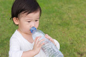 Little asian girl  drinking water from plastic bottle — Stock Photo