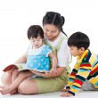 Young female with two little asian children reading a book — Stock Photo #64660883
