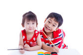 Children looking at the camera and smiling, holding a paintbrush — 图库照片