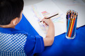 Little asian boy sitting at the table and drawing by colour penc — Stok fotoğraf
