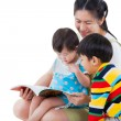 Young female with two little asian children reading a book — Stock Photo #70350899