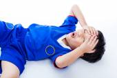 Youth asian soccer player with painful in forehead. On white — Stock Photo