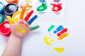 Child paint her palm with smiling face various colors. Studio sh — Stock Photo