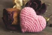 Pink knitted heart and dried red roses — Stock Photo