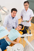 Assistant and patient at stomatology clinic — Stock Photo