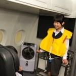 Little stewardess presenting life vest — Stock Photo #52172179