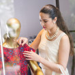 Brunette touching dress on the mannequin — Stock Photo #52172701