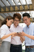 Asian friends busy with smartphones — Stock Photo