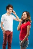 Vietnamese couple talking via mobile phone — Stock Photo