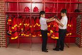Boys trying on fireman uniform — Stock Photo