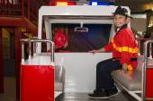 Little firefighters in the fire truck — Stock Photo