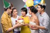 Girl receiving a birthday gift from her friends — Stock Photo