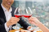 Couple clinking glasses of red wine — Stock Photo