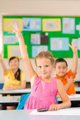 Schoolgirl raising hand at a lesson — Foto Stock
