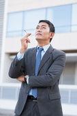 Businessman smoking cigarette — Stock Photo