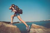 Tourist with backpack climbing a rock — Stock Photo