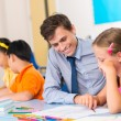 Elementary school teacher helping student — Stock Photo #52195005