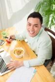 Businessman eating instant noodle soup — Stock Photo