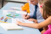 Teacher helping schoolgirl to draw a picture — Stock Photo
