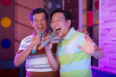 Asian senior men performing in karaoke bar — Stock Photo