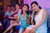 Ladies singing a song in karaoke bar — Stock Photo