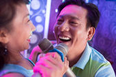 Aged Asian man singing a song in duet — Stock Photo