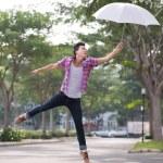 Asian man jumping with umbrella — Stock Photo #54310641