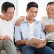 Grandfather, son and grandson reading book — Stock Photo #54315745