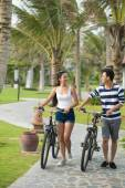 Couple walking with bicycles — Foto Stock