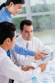 Business team analyzing statistics — Stock Photo