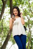 Beautiful Vietnamese girl texting — Stock Photo