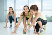 Fitness instructor adjusting position — Stock Photo