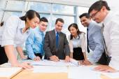 Business people discussing draft — Stockfoto