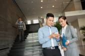 Vietnamese manager showing smartphone — Stock Photo
