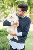 Hispanic man holding little dog — Zdjęcie stockowe