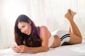 Woman lying on the bed and texting — Stock Photo