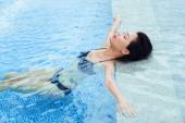 Brunette relaxing in the swimming pool — Stock Photo