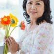 Mature woman with flowers — Stock Photo #56934897
