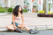 Woman in roller skaters sitting on the pavement — Stock Photo