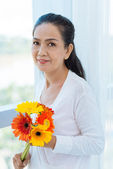 Senior woman holding a bouquet of gerberas — Foto de Stock