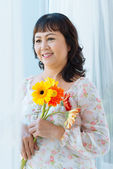 Smiling woman with flowers — Stock Photo