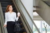 Businesswoman going down the escalator — Стоковое фото