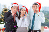 Coworkers with party blowers — Stock Photo