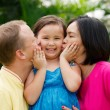 Parents kissing daughter — Stock Photo #63672605